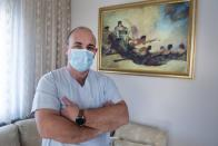 In this Saturday, Dec. 12, 2020 photo, Gabriel Tachtatzoglou poses at his house in Agios Athanassios, outside Thessaloniki city, northern Greece. Tachtatzoglou has worked as an ICU nurse in northern Greece for 20-years but when the pandemic struck his city in the fall, COVID-19 wards were quickly overwhelmed. He saw little choice other than to treat sick members of his family at home, setting up a treatment site with borrowed and rented medical machinery and using a hat stand to hold IV bags. (AP Photo/Giannis Papanikos)