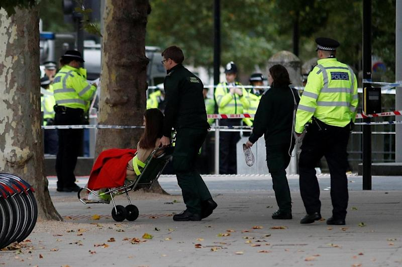 Emergency services personnel wheel a woman in a wheelchair to a nearby ambulance near the Natural History Museum (REUTERS)