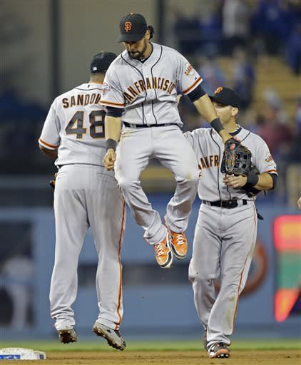 San Francisco Giants including centerfielder Angel Pagan, center, celebrate their 5-3 win voer the Los Angeles Dodgers in a baseball game in Los Angeles Wednesday, April 3, 2013. (AP Photo/Reed Saxon)