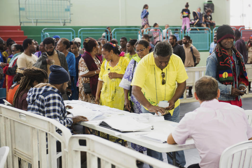 People attend a referendum in Noumea, New Caledonia, Sunday, Oct. 4, 2020, whether voters choose independence from France. Voters in New Caledonia, a French archipelago in the South Pacific, are deciding Sunday whether they want independence from France in a referendum that marks a milestone in a three-decade decolonization effort. (AP Photo/Mathurin Derel)