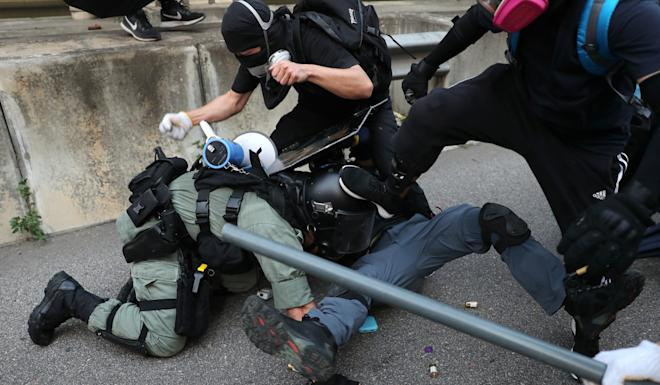 An officer making an arrest is attacked by several other protesters. Photo: Sam Tsang