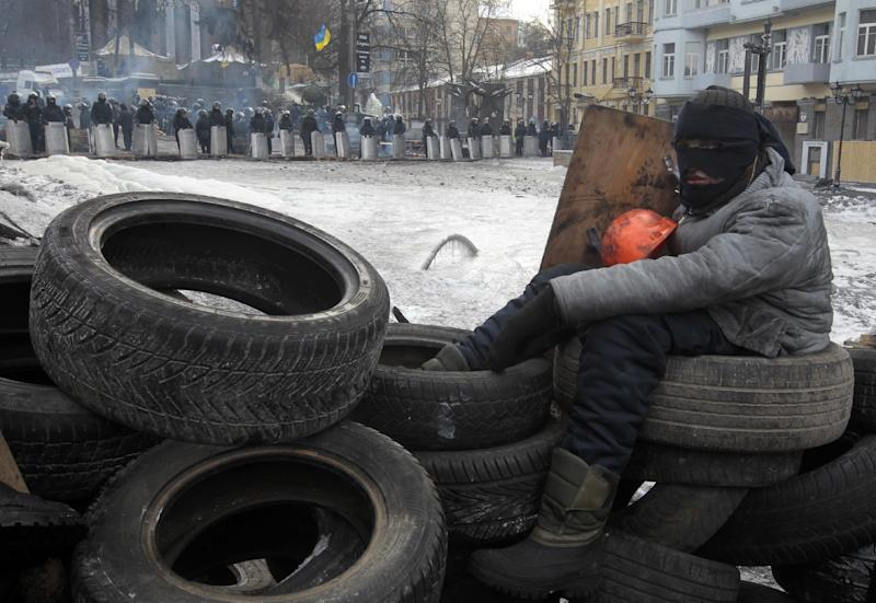 A protester mans the barricade in front of riot police in Kiev, Ukraine, Saturday, Feb. 1, 2014. Ukraine's embattled president Viktor Yanukovych is taking sick leave as the country's political crisis continues without signs of resolution.(AP Photo/Sergei Chuzavkov)