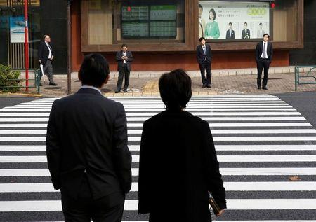 Pedestrians stand in front of an electronic board showing stock and foreign currency markets information outside a brokerage in Tokyo, Japan, December 1, 2016. REUTERS/Kim Kyung-Hoon