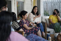 In this Friday, Sept. 24, 2021, photo Democratic congressional candidate Rochelle Garza, second from right, holds a conversation over issues at a backyard house party in Brownsville, Texas. A push for climate change could create political liabilities in energy rich areas. That includes South Texas, where many Latino voters already turned against Democrats during last year's presidential election — and where winning them back could prove critical to the party's hopes of retaining control of Congress during next year's midterms.(AP Photo/Eric Gay)