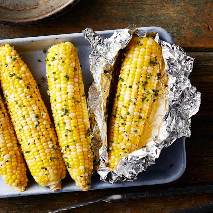 <p>This flavorful corn couldn't be easier to prepare. Just cover the ears of corn in a quick garlic-and-chive-flavored butter and wrap in foil and they're ready to throw on the grill at home or over coals at the campsite.</p>