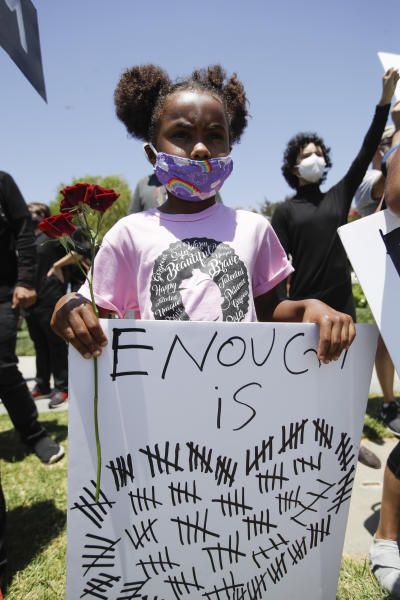 Sabrina Murphy, 6, holds a sign Thursday June, 4, 2020 in Santa Clarita, Calif., during a protest over the death of George Floyd who died May 25 after he was restrained by Minneapolis police. (AP Photo/Marcio Jose Sanchez)