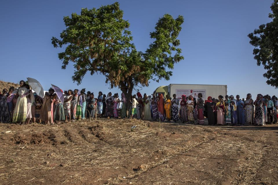 Tigray refugee women who fled the conflict in Ethiopia's Tigray region, wait in line to receive dignity kits at Umm Rakouba refugee camp in Qadarif, eastern Sudan, Tuesday, Nov. 24, 2020. (AP Photo/Nariman El-Mofty)