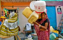 NEW DELHI, INDIA - JUNE 3: A woman carries her empty containers as she waits to fetch drinking water from municipal tankers, at Chanakyapuri on June 3, 2019 in New Delhi, India. The water and sewage utility is supplying 900 MGD (million gallons a day) of water against the requirement of 1200 MGD. With hot summer Water crisis is one of the biggest challenge many residents of Delhi has been grappling now days. (Photo by Amal KS/Hindustan Times via Getty Images)