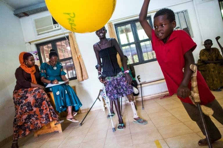 Nyakuatch Met (C), 14, and Kan Chol (R), 5, from Bentiu, South Sudan, both lost their left legs while fleeing their village due to the fighting