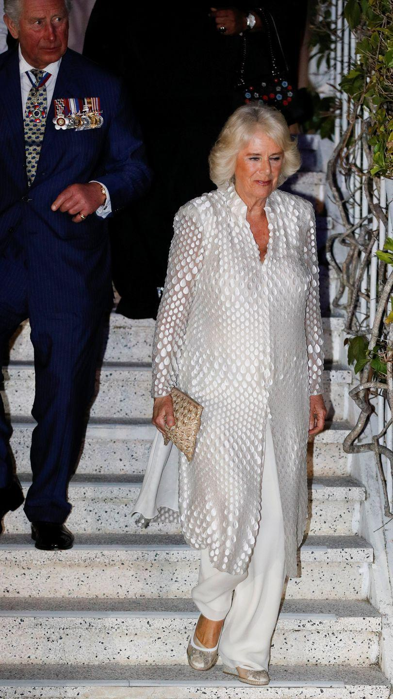 """<p>On the first night of <a href=""""https://www.townandcountrymag.com/society/tradition/g26850147/prince-charles-camilla-parker-bowles-royal-tour-caribbean-2019-photos/"""" rel=""""nofollow noopener"""" target=""""_blank"""" data-ylk=""""slk:Camilla and Charles's Caribbean tour"""" class=""""link rapid-noclick-resp"""">Camilla and Charles's Caribbean tour</a>, the Duchess paired a white sheer caftan with appliqué detailing, white wide-legged dress pants, and a wicker clutch for a dinner at Prime Minister's residence in Barbados. </p>"""