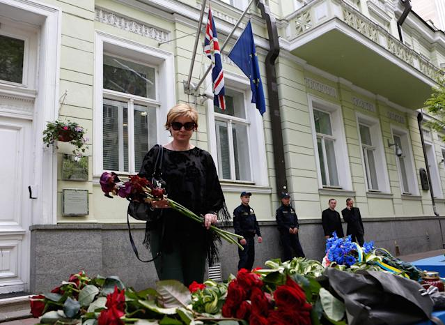 <p>A woman lays flowers in front of the British Embassy in Kiev, Ukraine, Tuesday, May 23, 2017. An apparent suicide bomber attacked an Ariana Grande concert as it ended Monday night in Manchester Arena killing over a dozen people among a panicked crowd of young concertgoers. (AP Photo/Sergei Chuzavkov) </p>