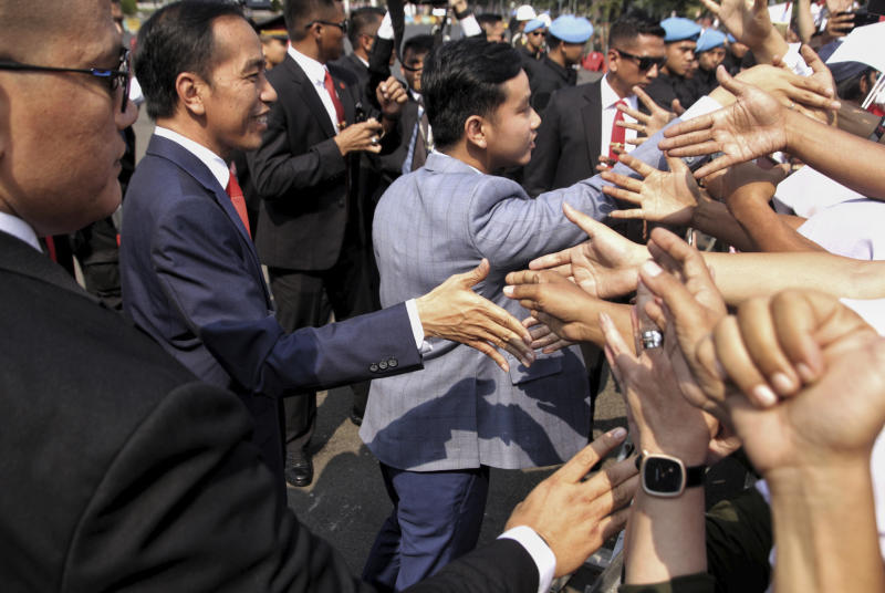 Indonesian President Joko Widodo, left, and his son, Gibran Rakabuming Raka, center, greet supporters prior to the inauguration for his second term, in Jakarta, Indonesia, Sunday, Oct. 20, 2019. Indonesian President Joko Widodo, who rose from poverty and pledged to champion democracy, fight entrenched corruption and modernize the world's most populous Muslim-majority nation, was sworn in Sunday for his second and final five-year term with a pledge to take bolder actions. (AP Photo)