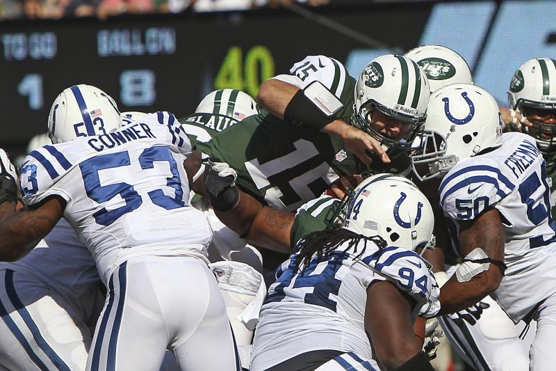 New York Jets quarterback Tim Tebow (15) dives for extra yards as Indianapolis Colts inside linebacker Kavell Conner (53), Drake Nevis (94) and Jerrell Freeman (50) tackle him during the first half of an NFL football game Sunday, Oct. 14, 2012, in East Rutherford, N.J. (AP Photo/Seth Wenig)