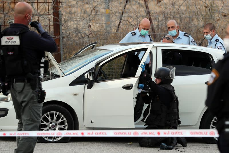 Israeli security forces survey a car at the scene of what Israeli police said was an attempted car-ramming attack at a checkpoint in East Jerusalem