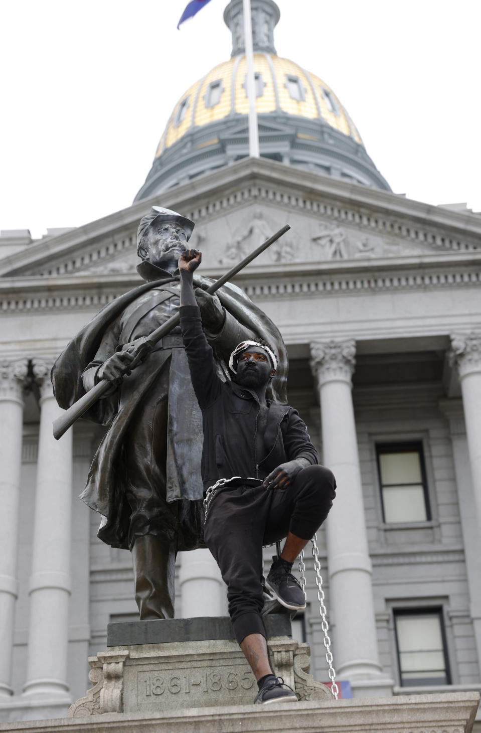 FILE - In this June 6, 2020 file photo, a demonstrator raises his fist after chaining himself to the Civil War Monument during protests over the death of George Floyd in front of the State Capitol in downtown Denver. On Thursday, Feb. 25, 2021, state lawmakers are considering what to put on the pedestal on which the monument stood until it was toppled in late June 2020. (AP Photo/David Zalubowski, File)