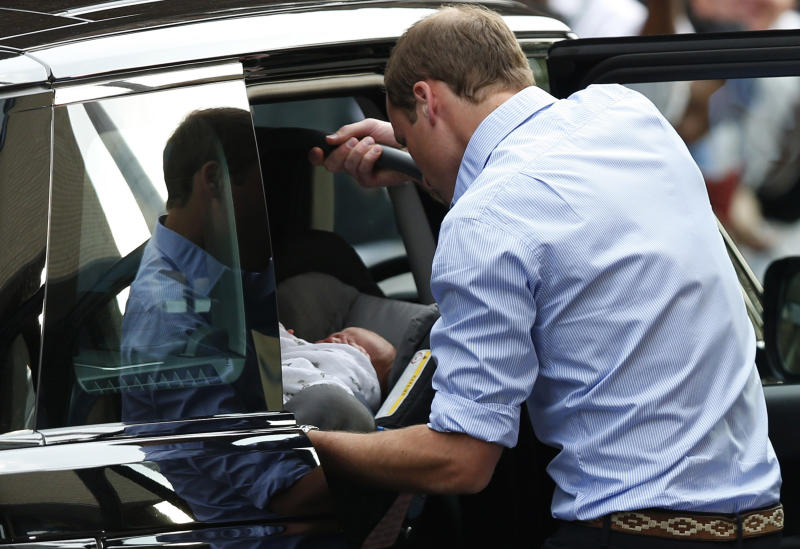 FILE - This is a Tuesday July 23, 2013 file photo of Britain's Prince William places carefully the Prince George of Cambridge into a car, Tuesday July 23, 2013, as they leave St. Mary's Hospital exclusive Lindo Wing in London where the Duchess gave birth on Monday July 22. Britain's Prince William has described his joy at introducing newborn son to the world on the steps of a London hospital last month and about his nerves about fitting the car seat securely into the Land Rover before driving off. (AP Photo/Sang Tan, File)