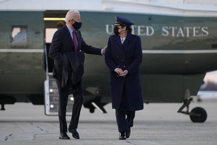 President Joe Biden speaks with a member of the U.S. Air Force after handing her a challenge coin as he walks to Air Force One at Andrews Air Force Base, Md., Friday, Feb. 5, 2021. Biden is spending the weekend at his home in Delaware. (AP Photo/Patrick Semansky)