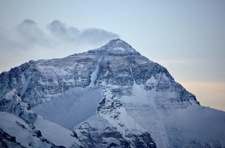 FILE PHOTO: Wind blows snow off the summit at dusk of the world's highest mountain Mount Everest, also known as Qomolangma, in the Tibet Autonomous Region