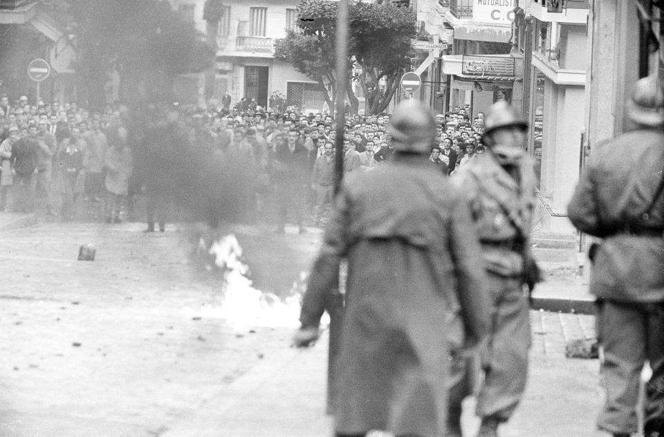 FILE - In this Dec.10, 1960 file photo, Algerian demonstrators watch as gasoline filled bottle burns in a street of Algiers, protesting the arrival of French President Charles De Gaulle in Algeria to promote his self-determination policy. French President Emmanuel Macron announced a decision to speed up the declassification of secret documents related to Algeria's seven-year war of independence from 1954 to 1962. (AP Photo, File)