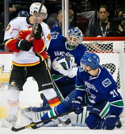 Vancouver Canucks goalie Cory Schneider, center, makes the save as Calgary Flames' Sven Baertschi, left, of Switzerland, looks for the rebound and Canucks' Mason Raymond defends during the first period of an NHL hockey game game in Vancouver, British Columbia, on Wednesday, Jan. 23, 2013. (AP Photo/The Canadian Press, Darryl Dyck)