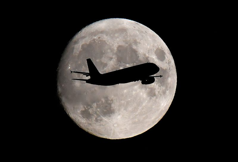 FILE PHOTO:  A passenger plane passes in front of the moon as it makes its final landing approach to Heathrow Airport in London