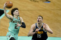Charlotte Hornets guard LaMelo Ball shoots over Denver Nuggets center Nikola Jokic during the second half of an NBA basketball game on Tuesday, May 11, 2021, in Charlotte, N.C. (AP Photo/Chris Carlson)