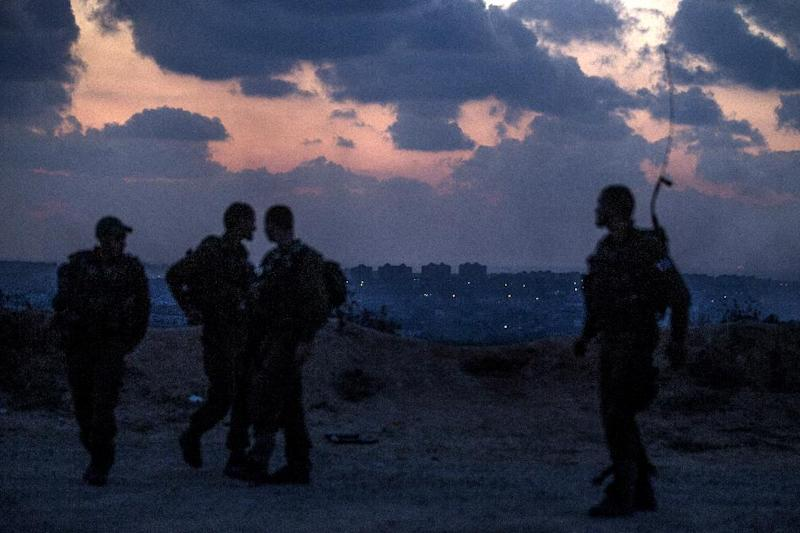 Israeli soldiers stand near the southern Israeli border with the Gaza Strip on July 17, 2014
