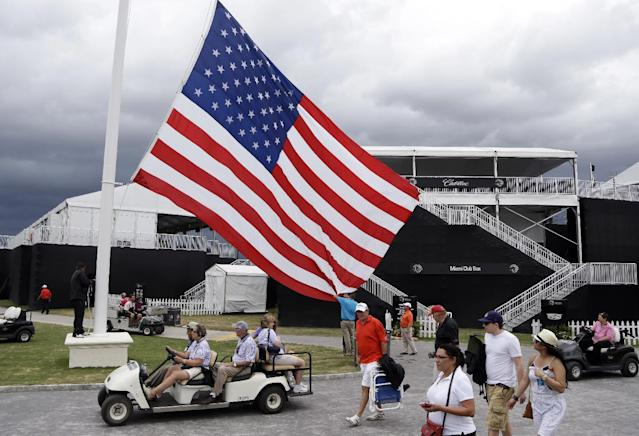 An American flag is lowered from a flag pole after play was suspended due to approaching inclement weather during the first round of the Cadillac Championship golf tournament, Thursday, March 6, 2014, in Doral, Fla. (AP Photo/Lynne Sladky)