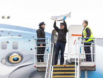 Alaska Airlines pilots hold up the first Copper River Salmon upon arrival in Seattle