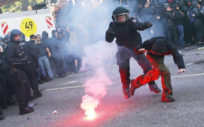 German riot policeman catches a protester during the demonstrations - Credit: Reuters