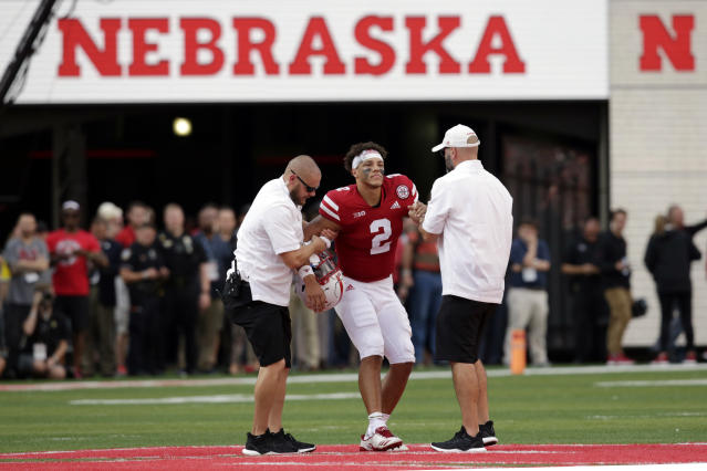 "Nebraska trainers help injured quarterback <a class=""link rapid-noclick-resp"" href=""/ncaaf/players/286944/"" data-ylk=""slk:Adrian Martinez"">Adrian Martinez</a> off the field during the second half against Colorado. Colorado won 33-28. (AP Photo/Nati Harnik)"