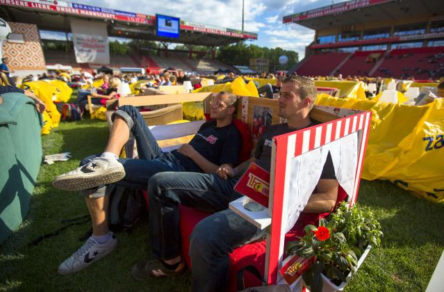 "People sit on sofas as they watch a 2014 World Cup soccer match during a public viewing event at the Alte Foersterei stadium in Berlin, June 15, 2014. Berlin's Union Berlin soccer team, which plays in the second division, has turned its stadium into a vast ""World Cup living room,"" allowing fans to transport their own sofa onto the pitch to watch the games for free. At least 12,000 people are expected to watch Germany's first World Cup game against Portugal on Monday, on up to 850 couches. Picture taken June 15, 2014. REUTERS/Thomas Peter (GERMANY - Tags: SPORT SOCCER WORLD CUP SOCIETY)"