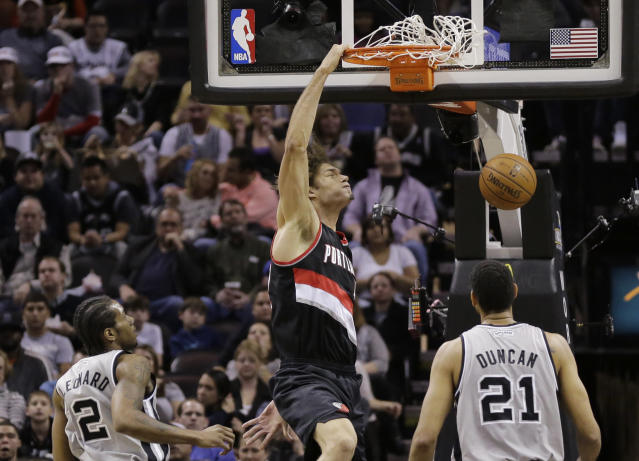Portland Trail Blazers' Robin Lopez, center, scores as San Antonio Spurs' Kawhi Leonard (2) and Tim Duncan (21) look on during the first half on an NBA basketball game, Friday, Jan. 17, 2014, in San Antonio. (AP Photo/Eric Gay)