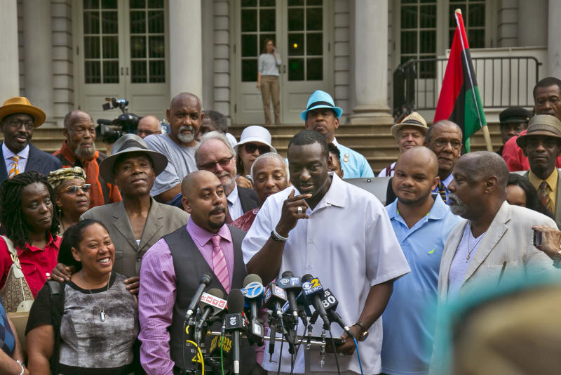 Surrounded by family and supporters, three of five men exonerated in the Central Park jogger rape case stand before microphones, Raymond Santana, second from left front, Yusef Salaam, center, and Kevin Richardson, second from right front, at a news conference in front of City Hall, Friday June 27, 2014 in New York. The New York City comptroller said Thursday that he has approved a tentative $40 million settlement with the five men, wrongly convicted in the 1989 Central Park jogger attack. (AP Photo/Bebeto Matthews)