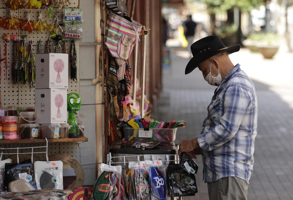 A vendor wearing a mask to protect against COVID-19 arranges merchandise at his business in San Antonio on Monday, July 20, 2020. Cases of COVID-19 continue to spike in Texas. / Credit: Eric Gay / AP