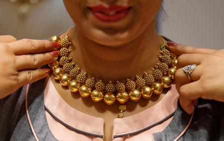 FILE PHOTO: A saleswoman displays a gold necklace to a customer inside a jewellery showroom on the occasion of Akshaya Tritiya, a major gold buying festival, in Mumbai