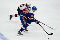 New Jersey Devils' Jack Hughes (86) defends against New York Islanders' Oliver Wahlstrom (26) during the third period of an NHL hockey game Thursday, May 6, 2021, in Uniondale, N.Y. The Devils won 2-1. (AP Photo/Frank Franklin II)