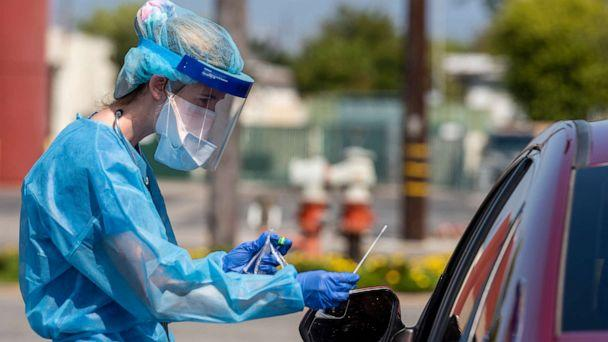PHOTO: A physician assistant with AltaMed Health Services prepares to test a drive-through patient for COVID-19 at their Bristol Street clinic in Santa Ana, Calif. on April 21, 2020. (Leonard Ortiz/Orange County Register via MediaNews Group via Getty Images)