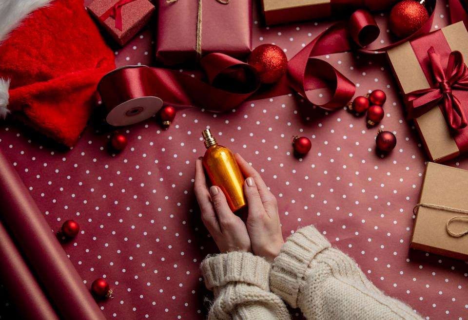 Woman hands hold perfume near gifts on wrapping paper