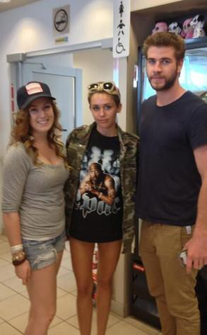 Although they haven't been seen together recently, Miley Cyrus posed with Liam Hemsworth and a fan following a hike in Canada, where she apparently wore her beloved 2Pac shirt and no pants.