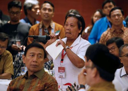 Bali bombing survivor Chusnul Khotimah (C) stand behind Indonesia Chief Security Minister Wiranto (L) as she speaks during a meeting between former militants and victims in Jakarta, Indonesia, February 28, 2018. REUTERS/Beawiharta