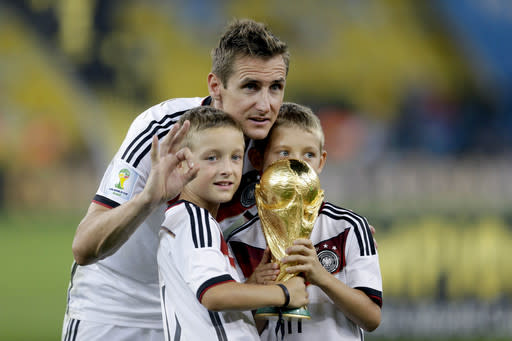 Germany's Miroslav Klose poses with the World Cup trophy and his sons following their 1-0 victory over Argentina after the World Cup final soccer match between Germany and Argentina at the Maracana Stadium in Rio de Janeiro, Brazil, Sunday, July 13, 2014. (AP Photo/Natacha Pisarenko)