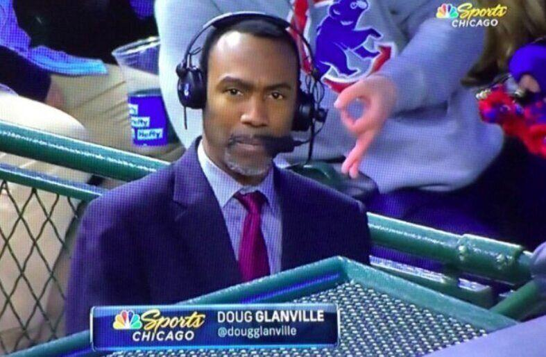 """The Chicago Cubs banned a fan from Wrigley Field """"indefinitely"""" for making this hand gesture behind Doug Glanville during a Cubs broadcast. (NBC Sports Chicago)"""
