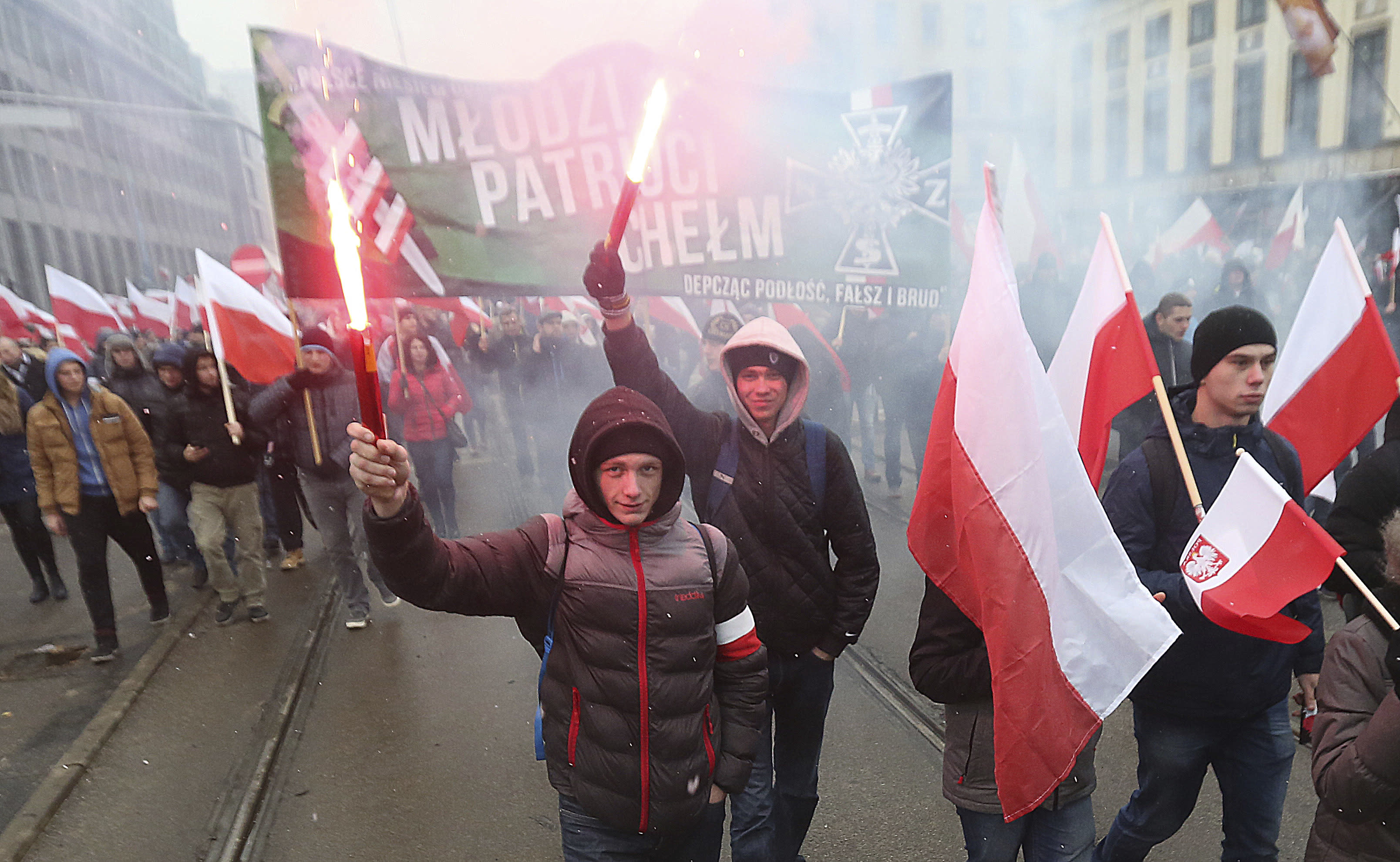 Nationalists, burning flares and carrying Polish flags as they march in large numbers through the streets of Warsaw to mark Poland's Independence Day in Warsaw, Poland, Friday, Nov. 11, 2016. (AP Photo/Czarek Sokolowski)