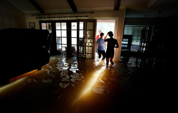 <p>A family that wanted to remain anonymous moves belongings from their home flooded by Harvey in Houston, Texas, Aug. 31, 2017. (Photo: Rick Wilking/Reuters) </p>