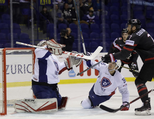 Henri Corentin Buysse of France, left, Pierre Crinon of France, center, challenge Canada's Sean Courtier, right, during the Ice Hockey World Championships group A match between Canada and France at the Steel Arena in Kosice, Slovakia, Thursday, May 16, 2019. (AP Photo/Petr David Josek)