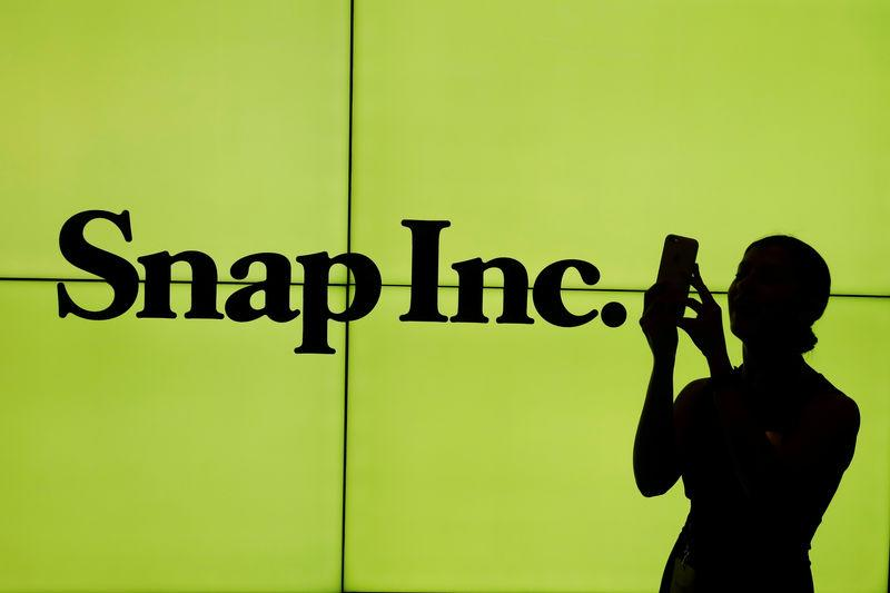 FILE PHOTO: A woman stands in front of the logo of Snap Inc. on the floor of the New York Stock Exchange (NYSE) while waiting for Snap Inc. to post their IPO, in New York City