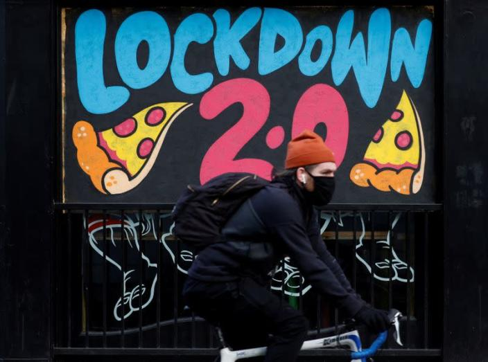 FILE PHOTO: A man cycles past a mural on the boarded up window of a closed pizza restaurant in Manchester