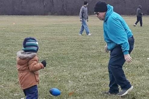 Bob Clay Sr. plays with his grandson, Christian Clay after the 2019 Turkey Bowl. (Photo by Colleen Ziemkowski)