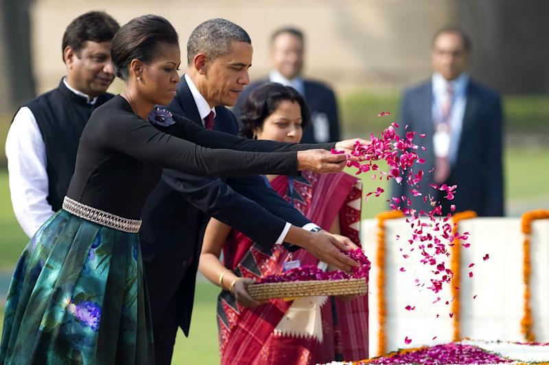 U.S. President Barack Obama and First Lady Michelle Obama spread rose petals as they participate in a wreath laying ceremony at Raj Ghat in New Delhi, India, Nov. 8, 2010. | Jim Watson–AFP/Getty Images